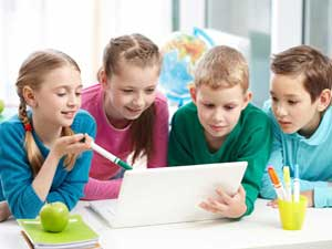 Four children looking at laptop
