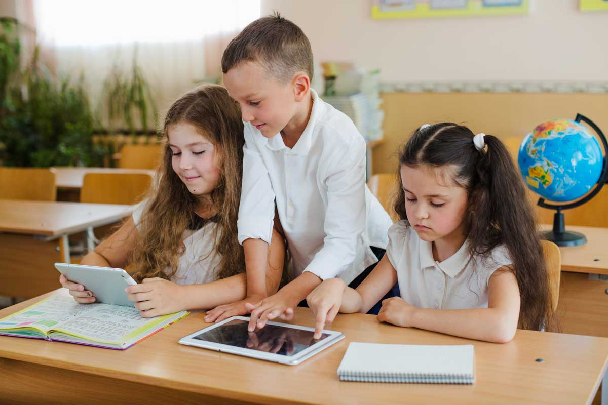 Three children working with IT devices